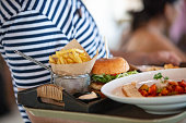 Unrecognizable waiter serving burger with fries at tourist resort