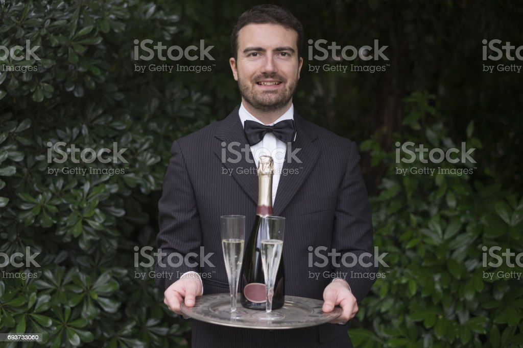 Waiter serving champagne flutes during a celebration stock photo