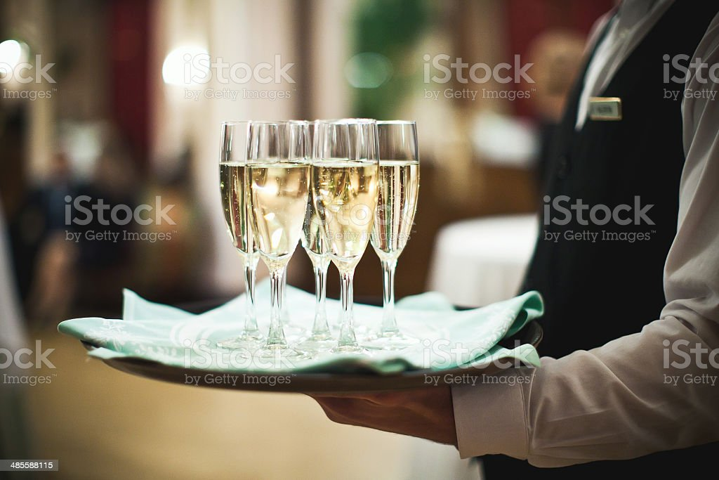 Waiter serving champagne on a tray stock photo