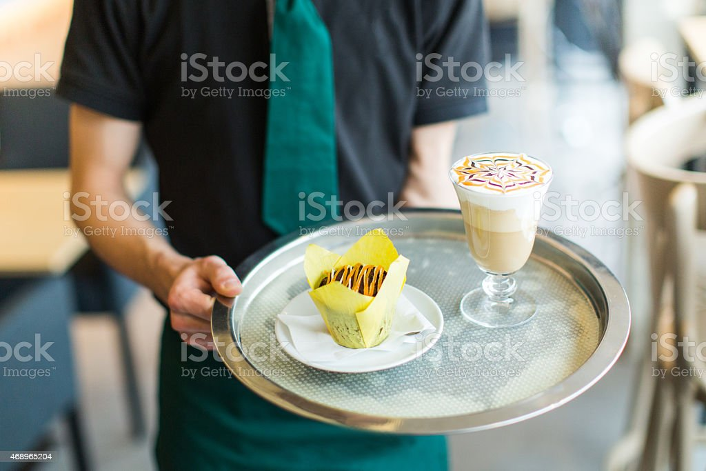 Waiter serving coffee drink and cupcake stock photo