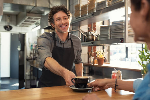 Waiter serving coffee to customer Smiling mature waiter giving hot coffee to woman at cafeteria. Happy man wearing black apron standing behind counter giving a cappuccino cup to woman in a coffee shop. Portrait of cheerful man serving happy customer at restaurant. old man working in a pub stock pictures, royalty-free photos & images