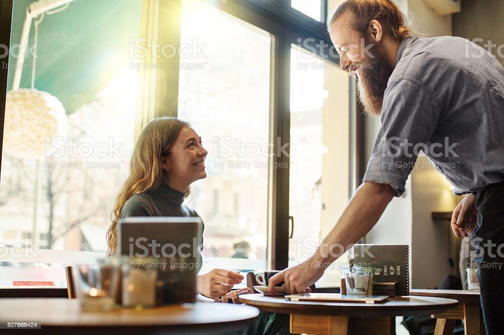 Waiter serving coffee to female customer stock photo