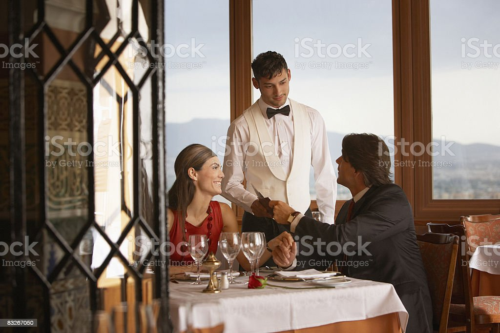 Waiter serving couple in elegant restaurant royalty-free stock photo