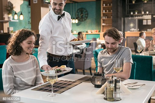 635812444 istock photo Waiter serving dishes to couple sitting at table in restaurant 831632204