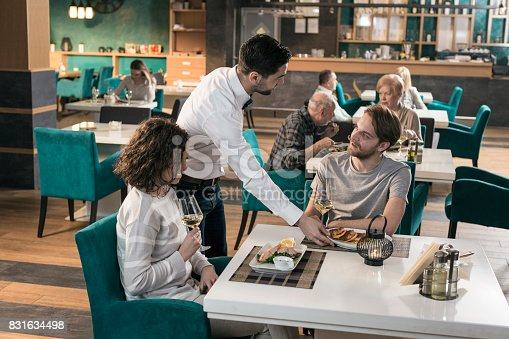 635812444 istock photo Waiter serving dishes to couple sitting at table in restaurant 831634498