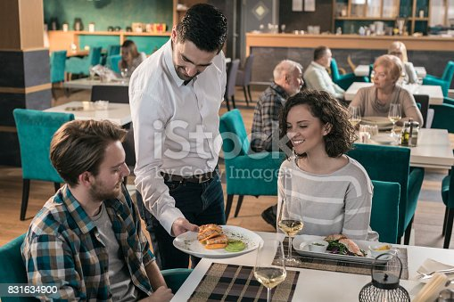 635812444 istock photo Waiter serving dishes to couple sitting at table in restaurant 831634900