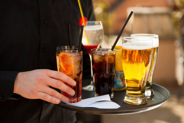Waiter serving drinks on the tray stock photo