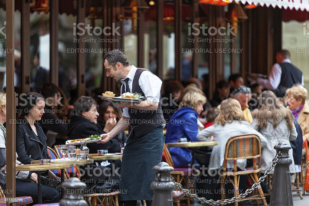 Waiter serving food in Cafe Le Bonaparte at Place...