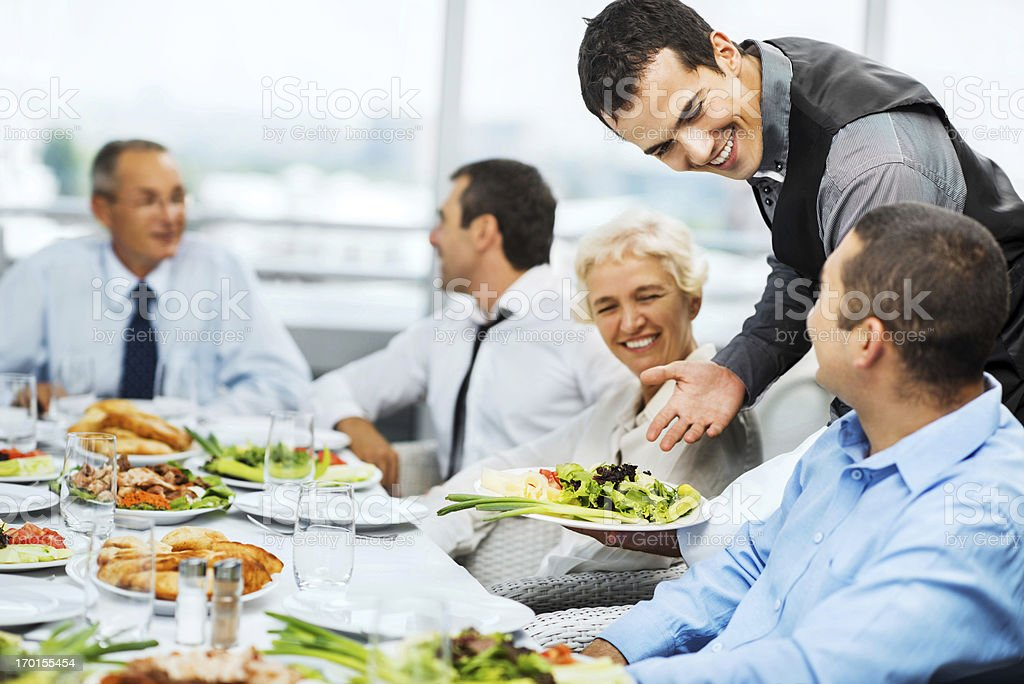 Waiter serving food to a group of business people. stock photo