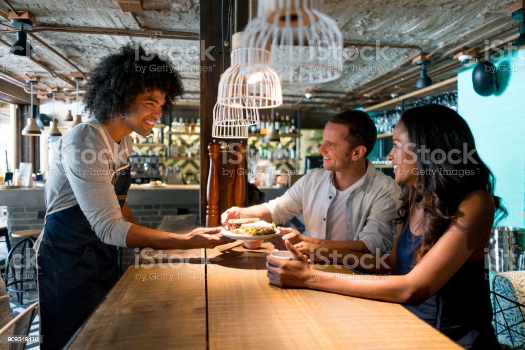 Waiter serving food to a happy couple at a restaurant - food service...