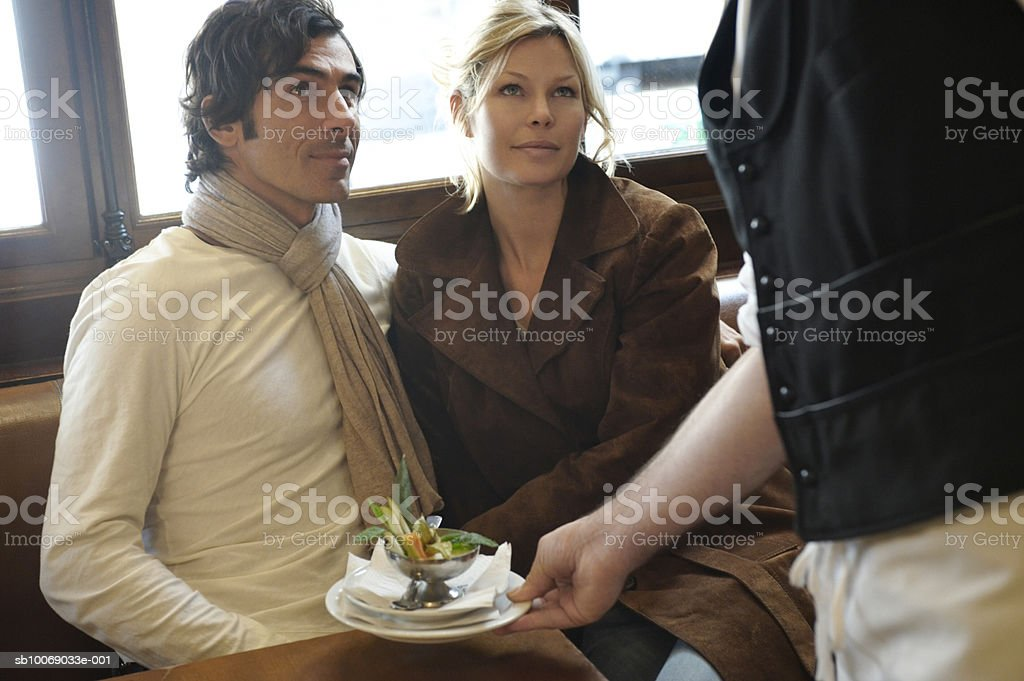 Waiter serving food to couple sitting at cafe foto de stock libre de derechos