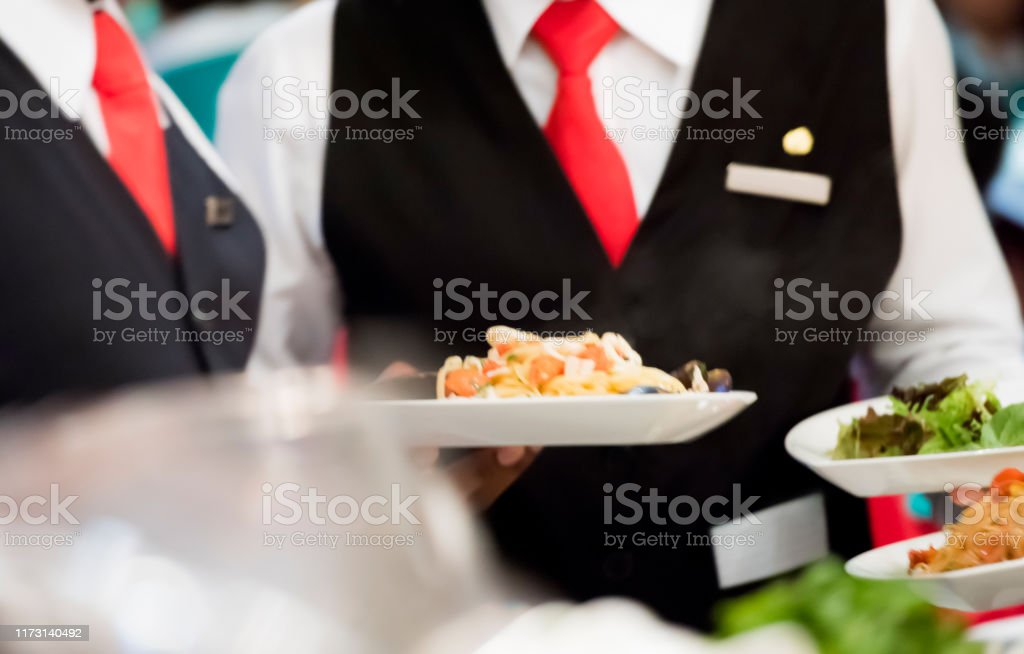 Close up photo of waiter in tie and uniform serving multiple plates...