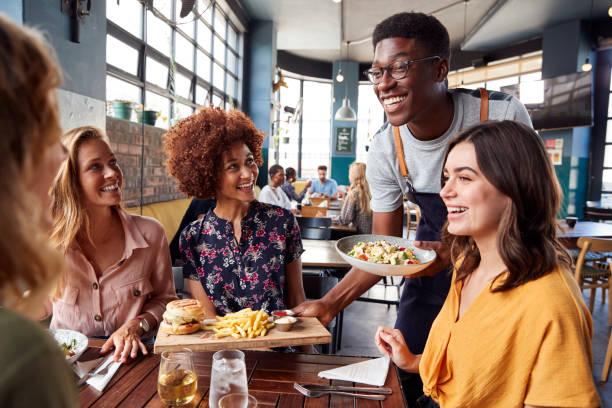 camarero sirviendo grupo de mujeres amigas reunión para bebidas y comida en el restaurante - restaurante fotografías e imágenes de stock