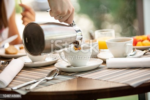 Waiter serving hot drink at hotel restaurant