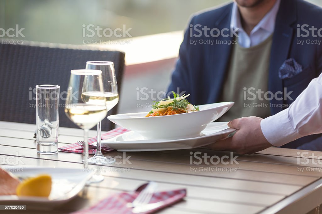 Waiter serving pasta in outdoor restaurant stock photo