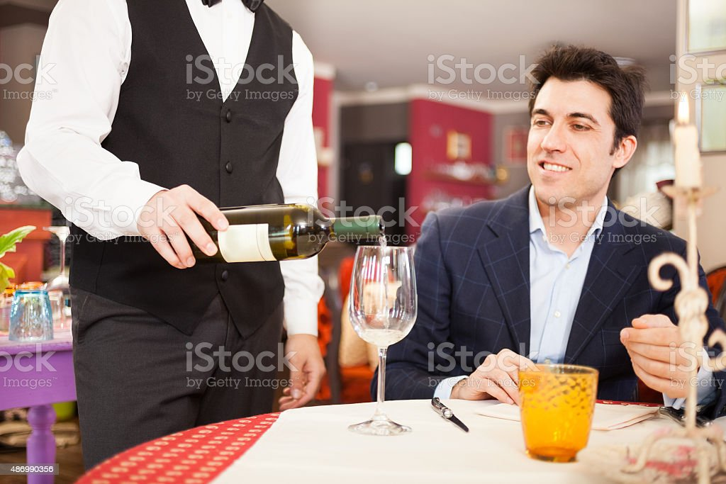 Waiter serving some wine to a man at the restaurant stock photo