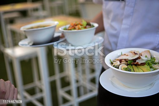 Close up photo of waiter serving soup to customer, selective focus