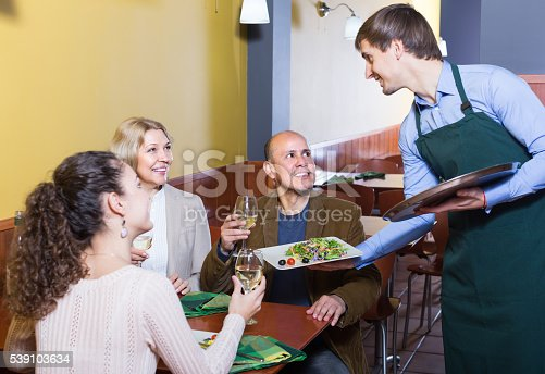 635812444 istock photo Waiter serving table in restaurant 539103634