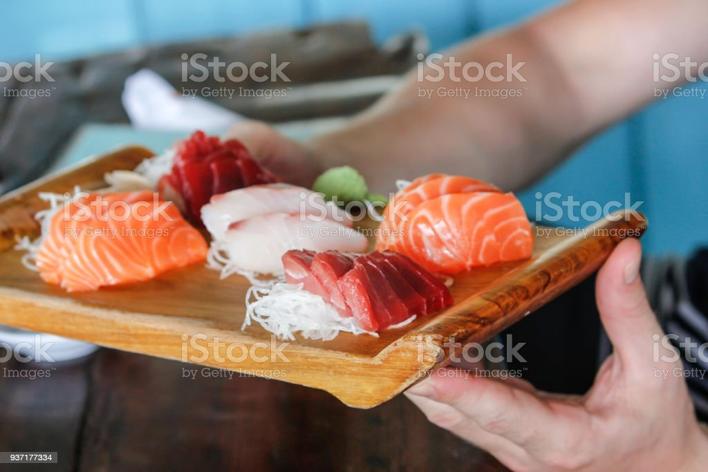 Waiter serving variation fresh sashimi slices stock photo