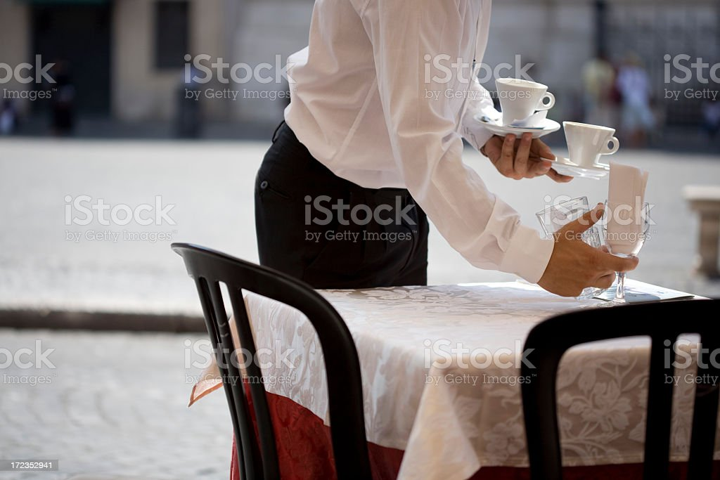 A waiter setting a table in a restaurant royalty-free stock photo