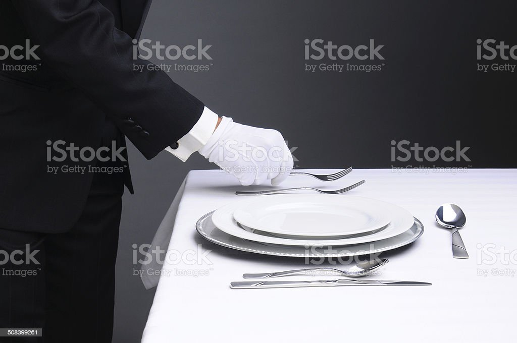 Waiter Setting Formal Dinner Table stock photo