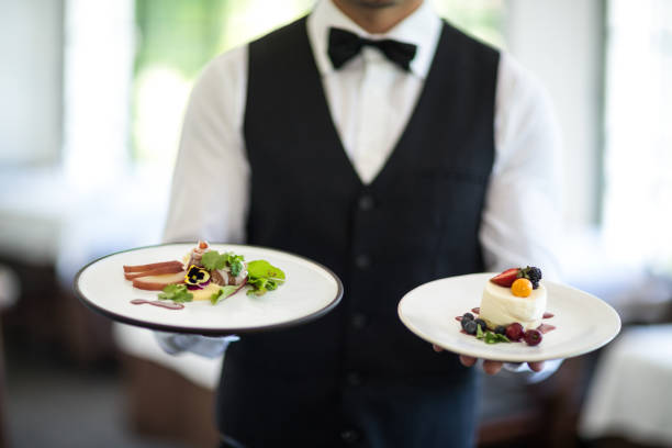 Waiter showing a dish Waiter showing a dish in a commercial kitchen waiter stock pictures, royalty-free photos & images