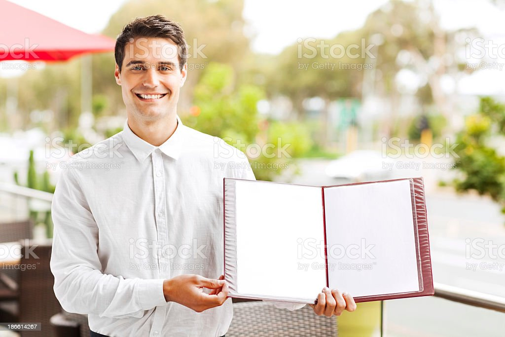 Waiter Showing Blank Menu In Restaurant royalty-free stock photo
