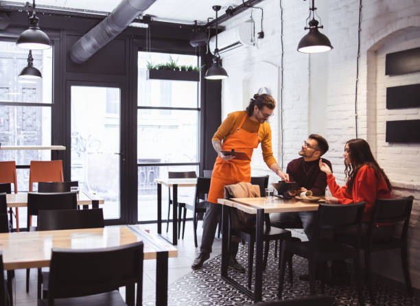 Waiter Takes Order From a young Couple stock photo