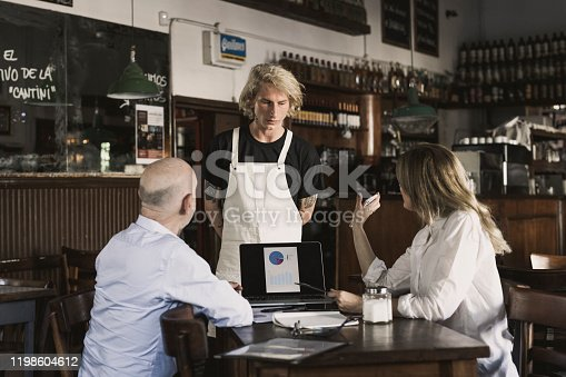 Woman showing from smartphone a picture from restaurants social media.