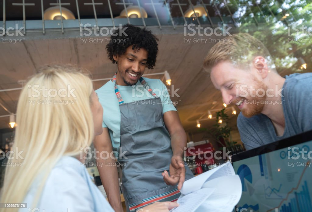 Waiter taking an order to a happy couple at a restaurant stock photo