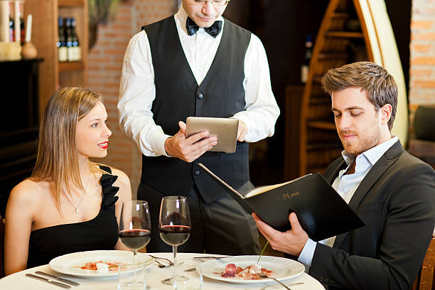 Waiter taking couple's order at a fancy restaurant stock photo