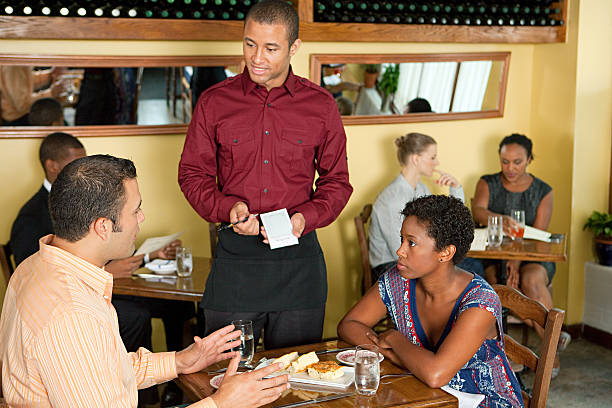 Waiter taking customer orders in restaurant stock photo