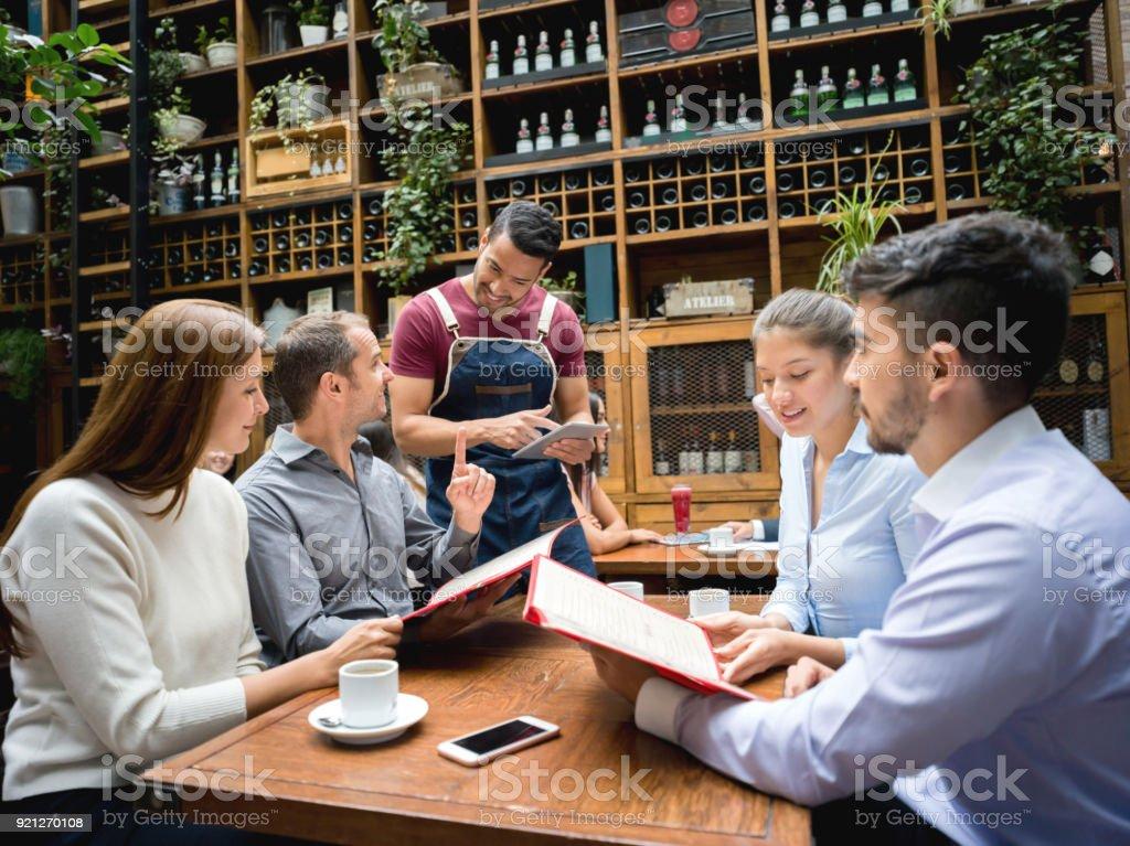 Garçon prenant commande à un groupe dans un restaurant à l'aide d'une tablette - Photo