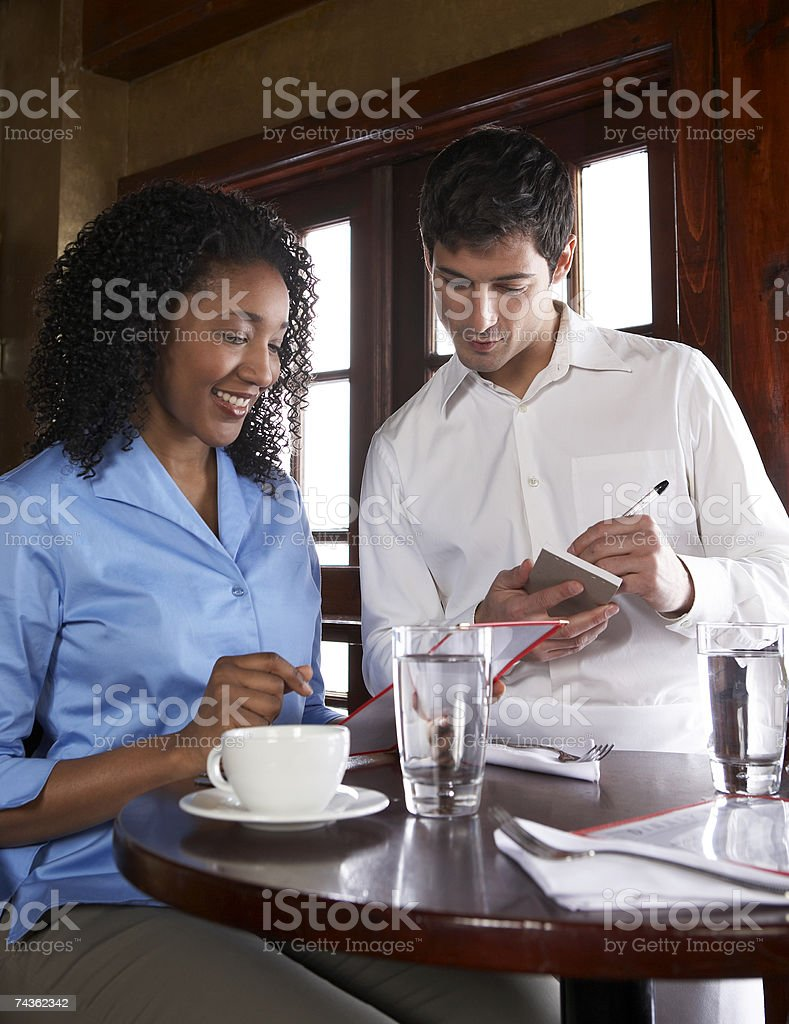 Waiter taking womans order in restaurant royalty-free stock photo