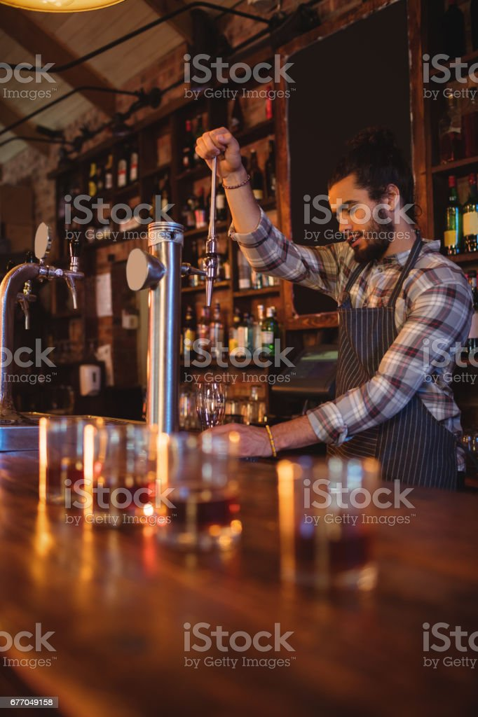 Waiter using beer tap at counter stock photo