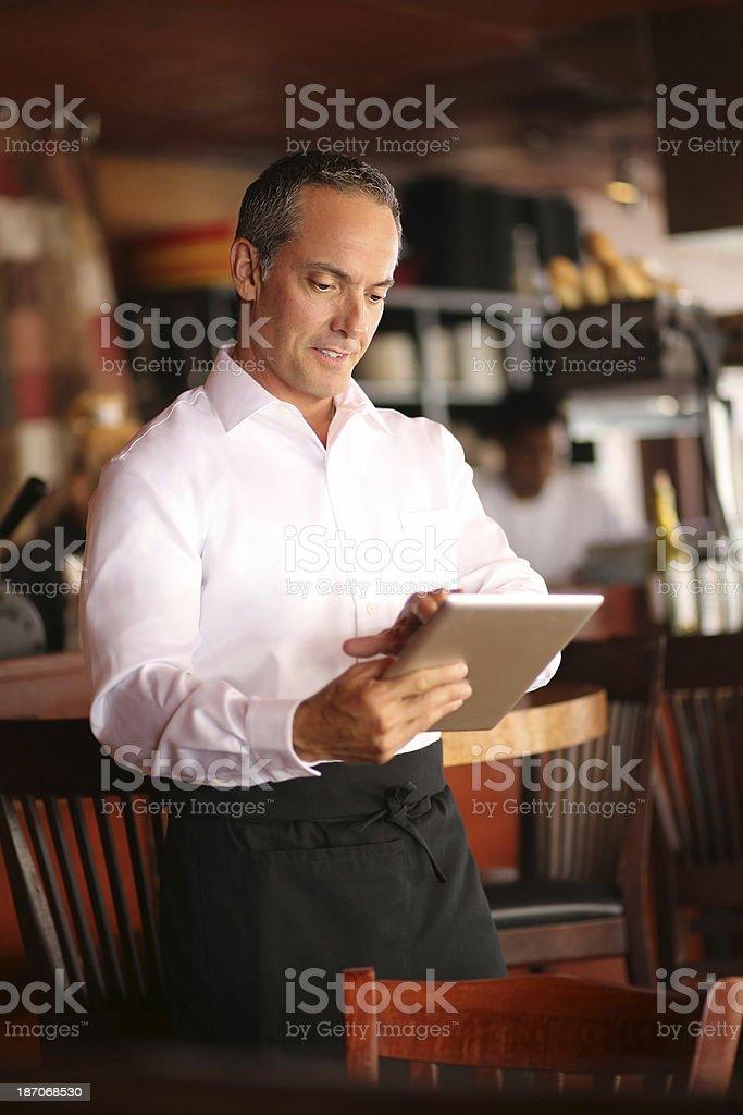 Waiter Using Digital Tablet In Restaurant stock photo