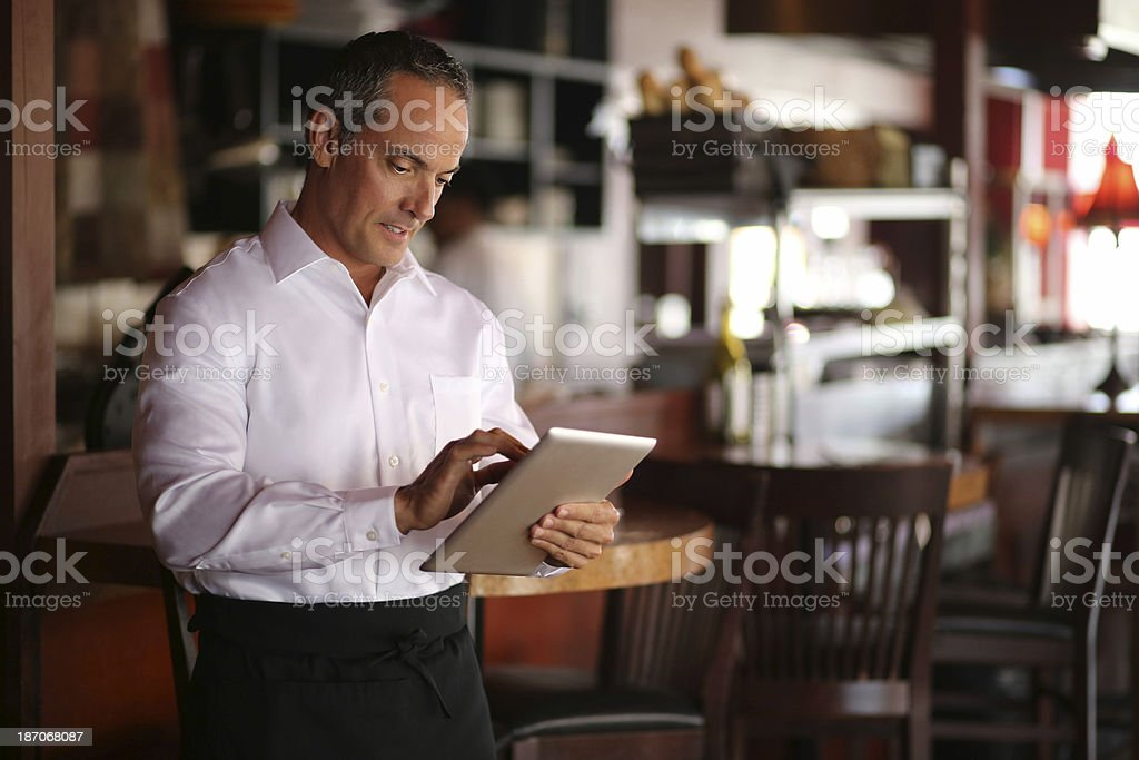 Waiter Using Tablet Computer In Restaurant stock photo