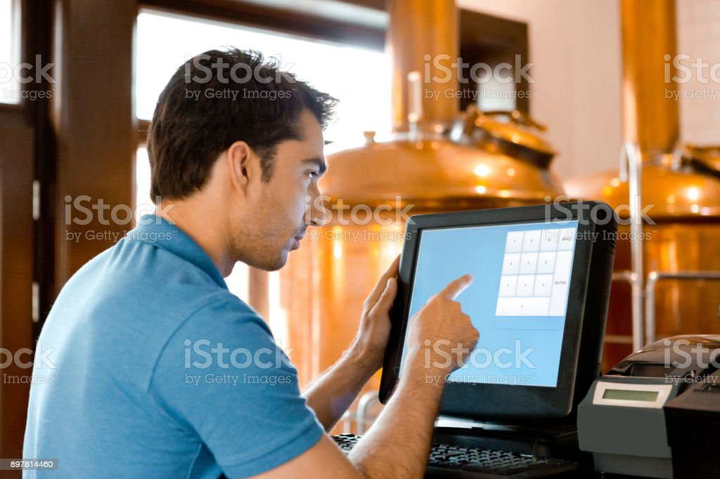 Waiter using touchscreen computer at the micro brewery bar counter Waiter using touchscreen computer at the micro brewery bar counter. Barter tender taking order using touch screen computer. Adult Stock Photo
