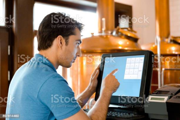 Waiter Using Touchscreen Computer At The Micro Brewery Bar Counter Stock Photo - Download Image Now
