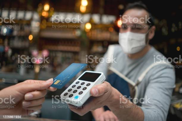 Waiter wearing a facemask while getting a contactless payment at a picture id1225861934?b=1&k=6&m=1225861934&s=612x612&h=dgbmgv lubzcjxc955hgds99dqapwbytuvsblmrzcre=
