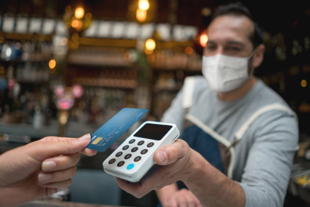Waiter wearing a facemask while getting a contactless payment at a restaurant stock photo