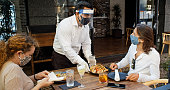istock Waiter Wearing PPE During Covid-19 Pandemic Serving Food to Diners Wearing Masks 1264166886