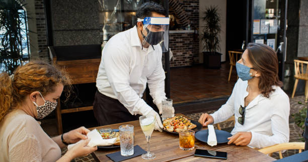 camarero usando epi durante covid-19 pandemic serving food to diners wearing masks - restaurante fotografías e imágenes de stock