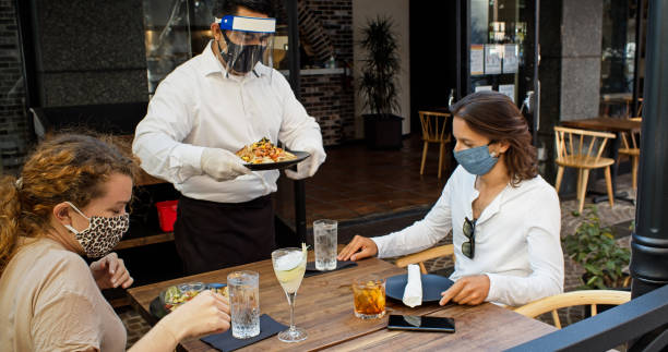 Waiter Wearing PPE During Covid-19 Pandemic Serving Plates of Food to Masked Diners