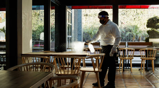 Waiter Wearing PPE During Covid-19 Pandemic Spraying Tables