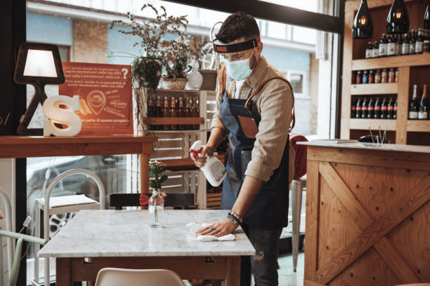 Waiter wearing protective face mask and face shield disinfecting tables in the restaurant stock photo