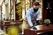 istock Waiter wearing protective face mask while disinfecting tables at outdoor cafe. 1227370547