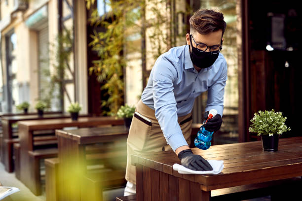 Waiter wearing protective face mask while disinfecting tables at outdoor cafe. stock photo