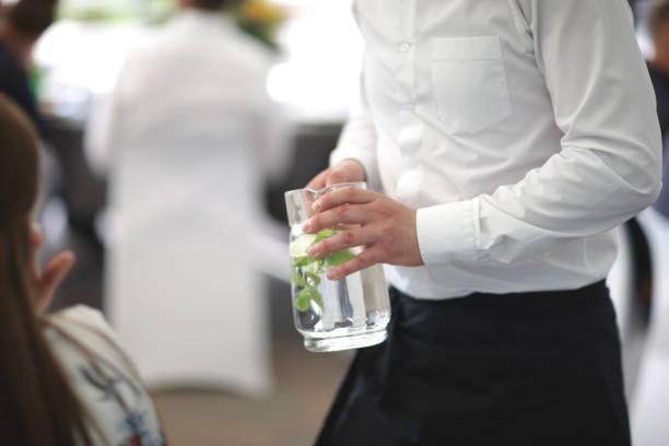 Kellner mit Krug mit erfrischendem Getränk – Foto