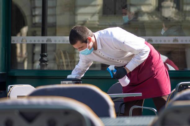 waiter with a mask disinfects the table of an outdoor bar, café or restaurant - covid restaurant imagens e fotografias de stock